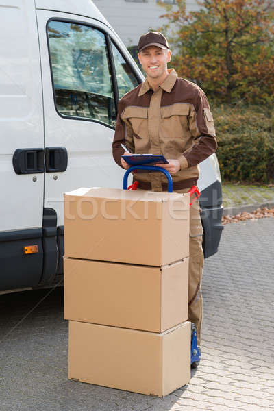 Confident Delivery Man With Parcels And Clipboard On Street Stock photo © AndreyPopov
