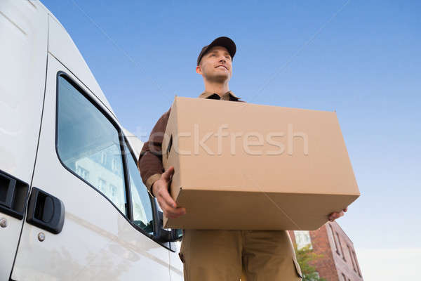 Delivery Man Carrying Cardboard Box By Truck Against Sky Stock photo © AndreyPopov