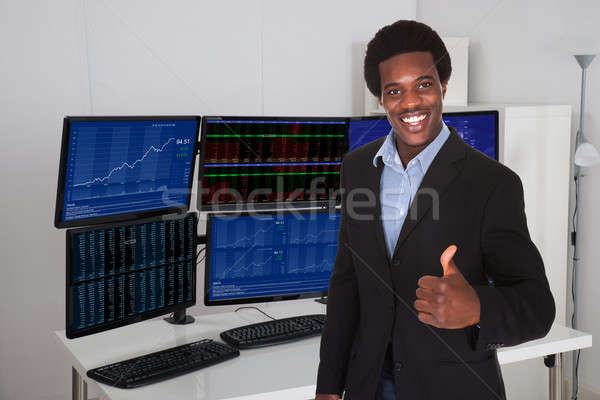 Stock Broker Gesturing Thumbs Up Against Multiple Monitors Stock photo © AndreyPopov