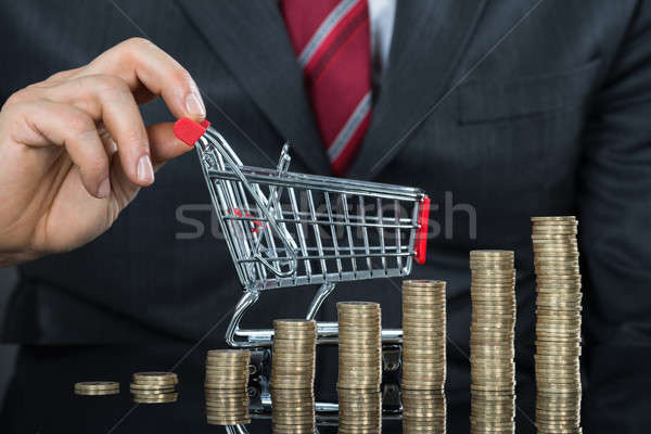 Close-up Of Businessman With Stack Of Coins And Shopping Cart Stock photo © AndreyPopov