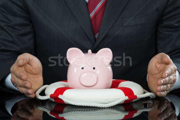 Close-up Of Businessman Hand Protecting Piggybank With Lifebelt Stock photo © AndreyPopov