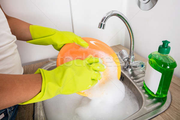 Person Washing Plate On Soapy Water Stock photo © AndreyPopov