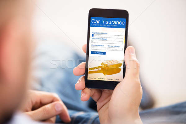 Man Filling Car Insurance Form On Mobile Phone Stock photo © AndreyPopov