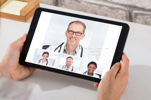 Person Videoconferencing With Doctors On Digital Tablet Stock photo © AndreyPopov
