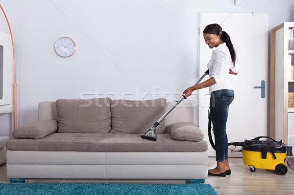 Africano mulher limpeza sofá aspirador de pó feliz Foto stock © AndreyPopov