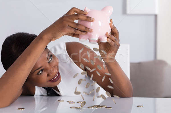 Woman Dropping Coins From Piggybank Stock photo © AndreyPopov
