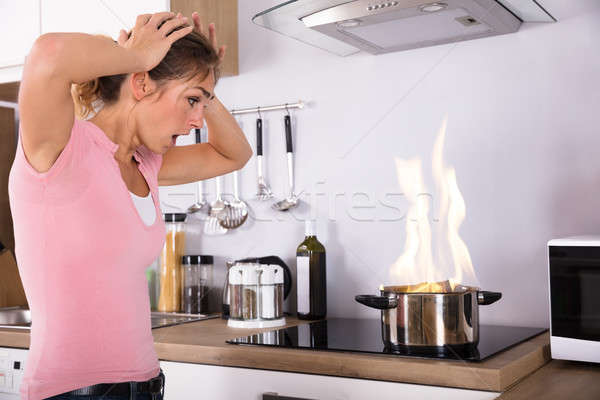 Stock photo: Shocked Young Woman Looking At Cooking Pot On Fire