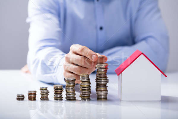 Increased Stack Of Coins In Front Of House Model Stock photo © AndreyPopov
