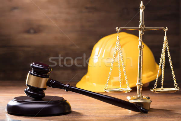 Gavel In Front Of Yellow Safety Helmet And Golden Scale Stock photo © AndreyPopov