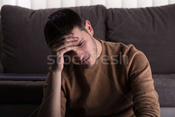 Sad Man Sitting In Front Of Sofa Stock photo © AndreyPopov