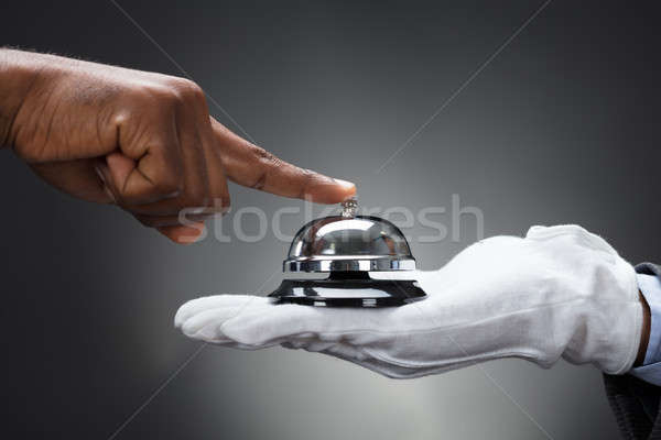 Customer Ringing Service Bell Held By Butler Stock photo © AndreyPopov