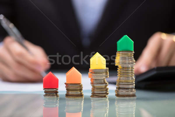 Businessperson Calculating Expenses In Front Of  House Models Stock photo © AndreyPopov