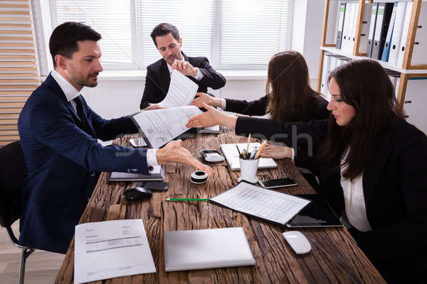 Businesspeople Discussing Paperwork In Office Stock photo © AndreyPopov