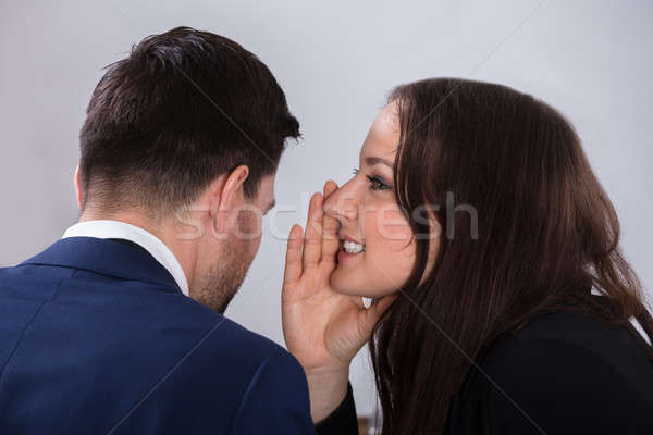 Businesswoman Whispering Into Partner's Ear Stock photo © AndreyPopov
