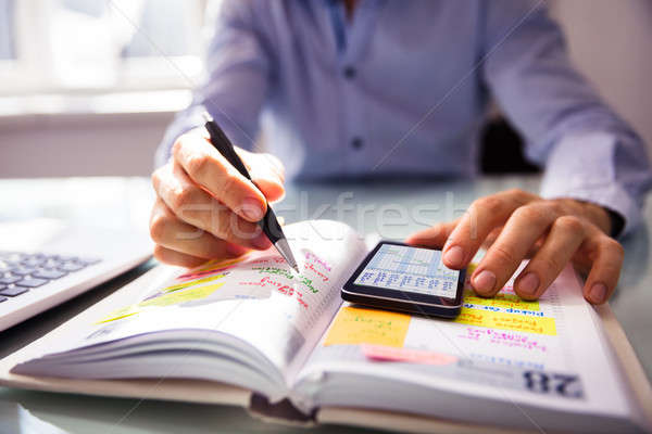 Stock photo: Businessperson Writing Schedule In Diary