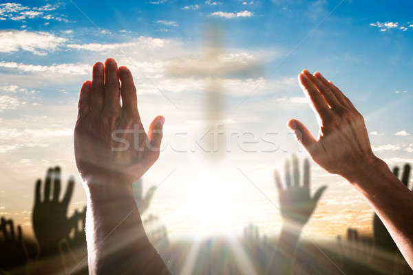 Human Hand Raising Hands With Cross In The Center Stock photo © AndreyPopov