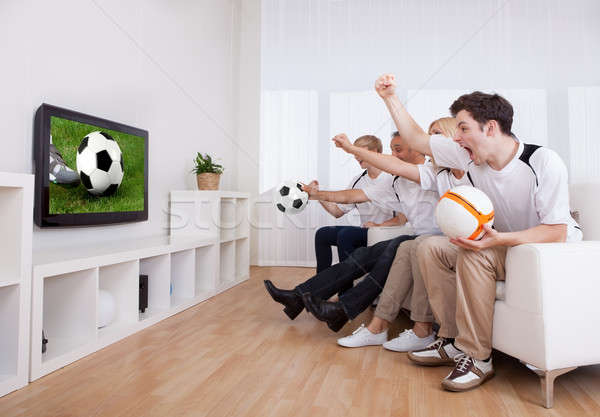 Jubilant family watching television Stock photo © AndreyPopov