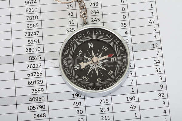 Compass on top of business data papers Stock photo © AndreyPopov