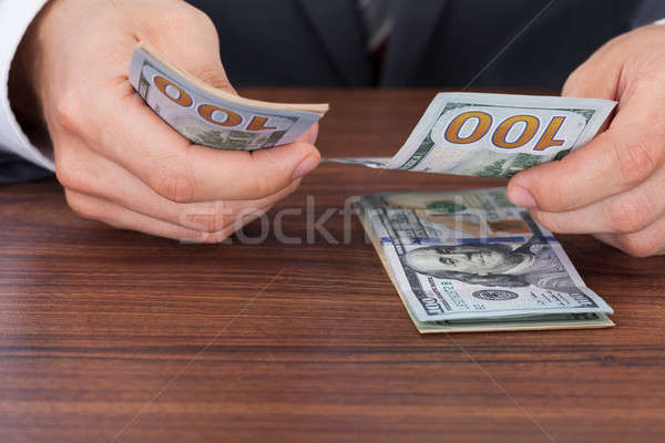 Stock photo: Businessman Counting Hundred Dollar Bills At Desk