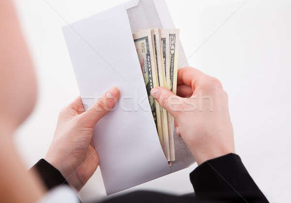 Businesswoman Putting American Banknotes In Envelope Stock photo © AndreyPopov