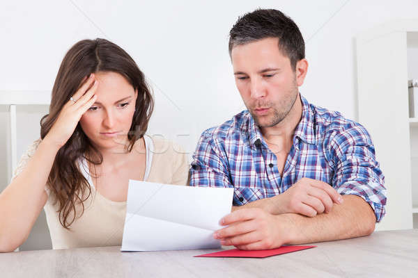Worried Couple Reading Paper Stock photo © AndreyPopov