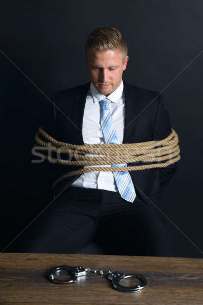 Businessman Tied With Rope Sitting In Front Of Table Stock photo © AndreyPopov
