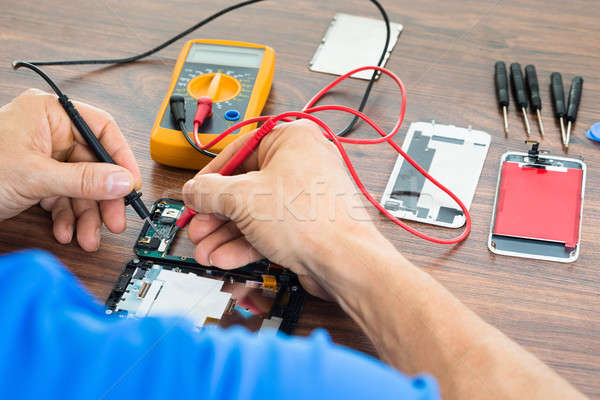 Technician Repairing Cellphone With Multimeter Stock photo © AndreyPopov
