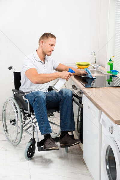Handicapped Man Cleaning Induction Stove Stock photo © AndreyPopov