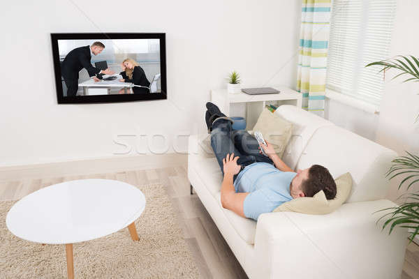 Relaxed Man Watching Movie In Living Room Stock photo © AndreyPopov