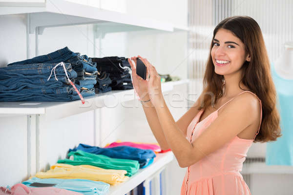 Happy Woman Photographing Garments In Retail Store Stock photo © AndreyPopov