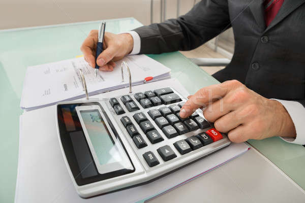 Close-up Of Businessman Calculating Invoice Using Calculator Stock photo © AndreyPopov