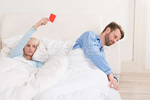 Woman Showing Red Card To Man In Bed Stock photo © AndreyPopov