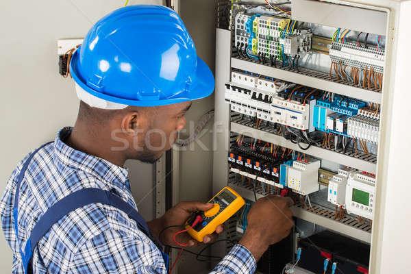 Technician Examining Fusebox With Multimeter Probe Stock photo © AndreyPopov