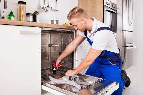 Repairman Fixing Dishwasher In Kitchen Stock photo © AndreyPopov