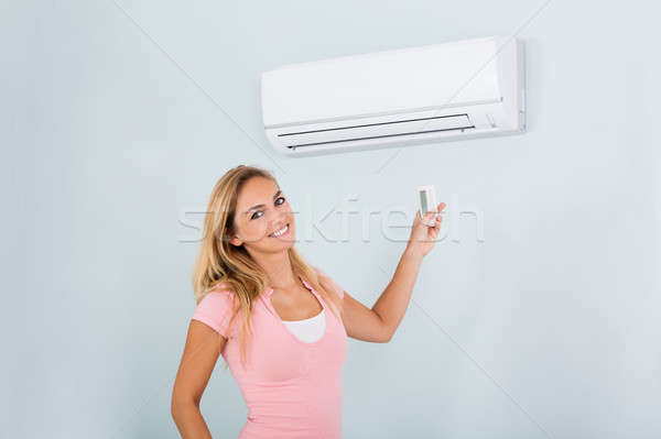Woman Operating Air Conditioner With Remote Stock photo © AndreyPopov