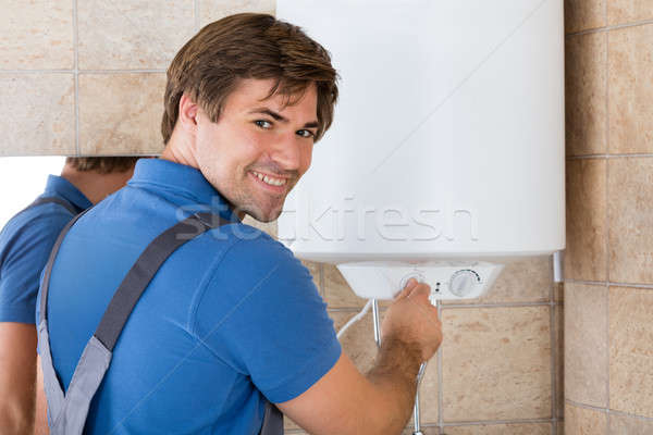Stock photo: Happy Young Repairman Holding Knob Of Electric Boiler