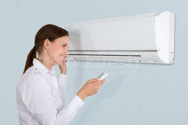 Stock photo: Businesswoman Using Air Conditioner