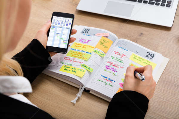 Businesswoman With Mobilephone Writing Schedule In Diary Stock photo © AndreyPopov