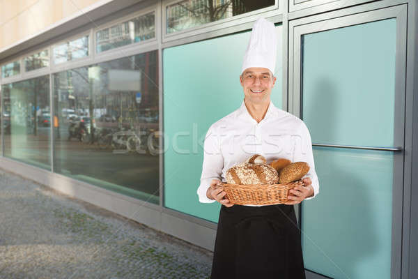 Souriant Baker panier plein pain Photo stock © AndreyPopov