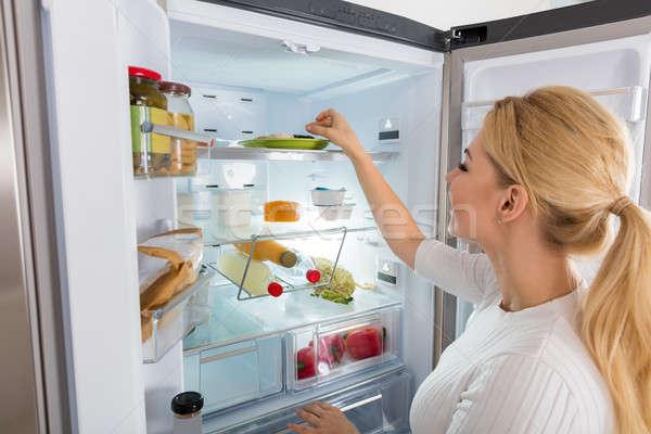 Kobieta żywności lodówce młoda kobieta Zdjęcia stock © AndreyPopov