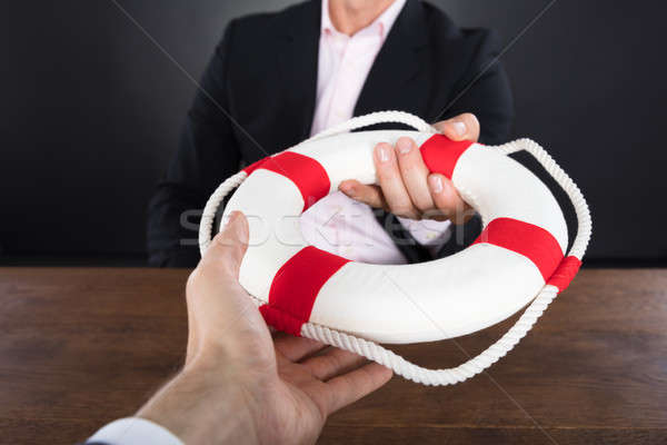 Businessman Passing A Lifebuoy To A Partner Stock photo © AndreyPopov