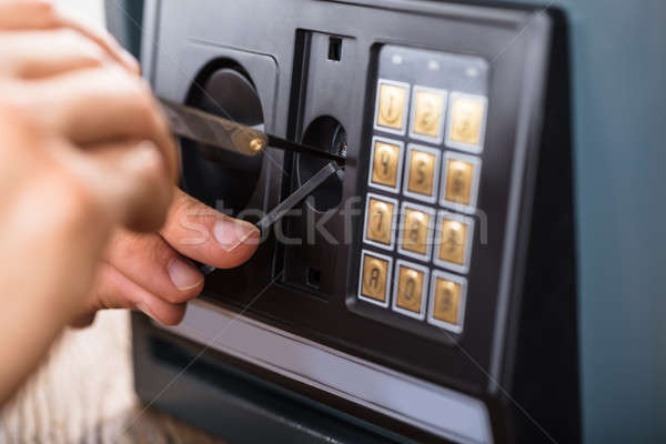 Hand Trying To Break Home Security Safe Stock photo © AndreyPopov