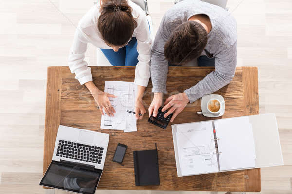 Overhead View Of Couple Calculating Bills Stock photo © AndreyPopov