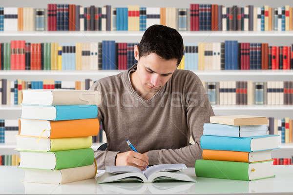 Fiatal férfi egyetemi hallgató tanul könyvtár könyvespolc Stock fotó © AndreyPopov