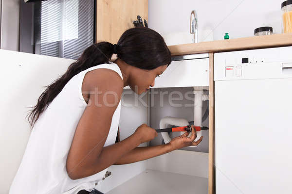 Woman Tightening Sink Pipe With Monkey Wrench Stock photo © AndreyPopov