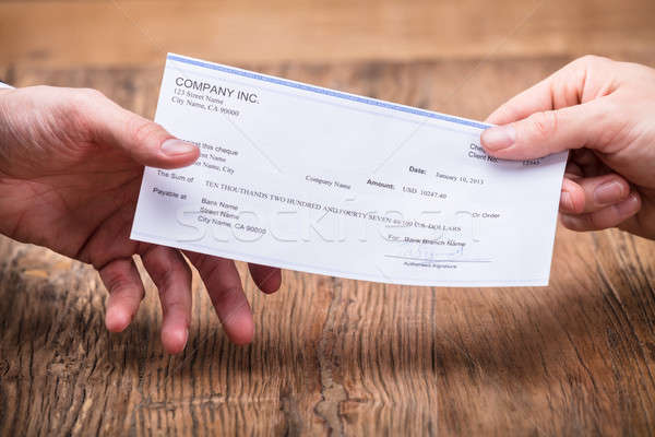 Businessperson's Hand Giving Cheque To Partner Stock photo © AndreyPopov
