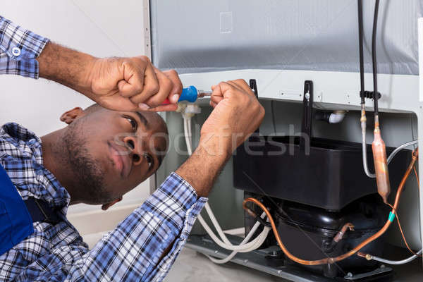 Male Serviceman Working On Fridge With Screwdriver Stock photo © AndreyPopov