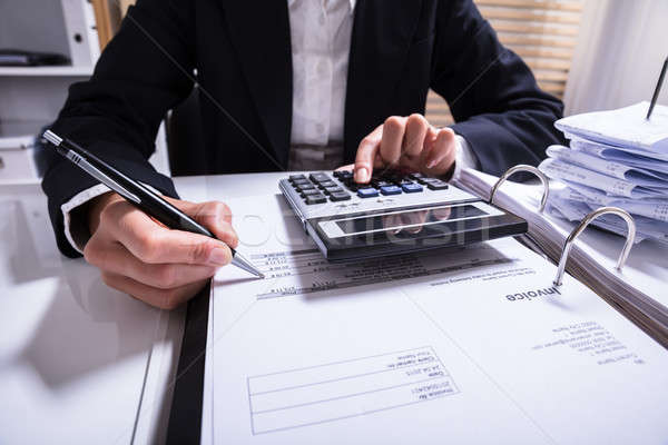 Midsection Of Businessperson Calculating Invoice Stock photo © AndreyPopov