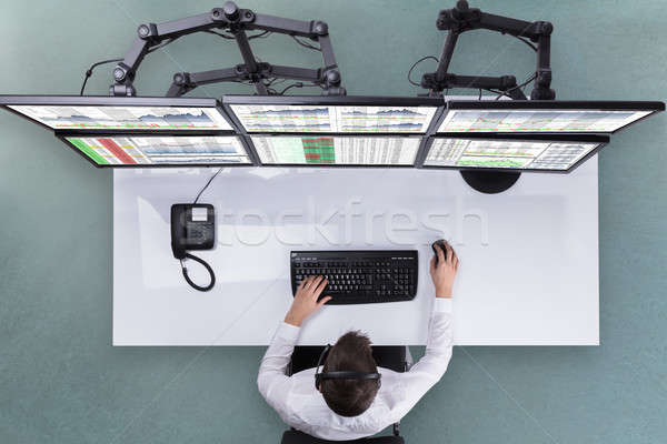 Male Stock Broker Analyzing Graphs On Multiple Computer Screen Stock photo © AndreyPopov