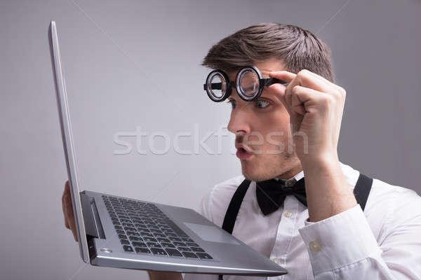 Сток-фото: молодым · человеком · глядя · ноутбука · экране · серый · компьютер